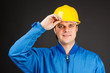 Young construction worker with his hand on hard hat brim