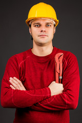 Portrait of a  young worker holding  pliers