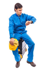 Worried construction worker looking at watch with serious expre