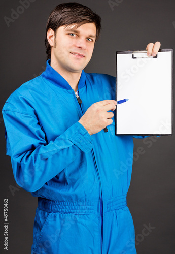 Portrait of young worker holding a pen and a blank clipboard