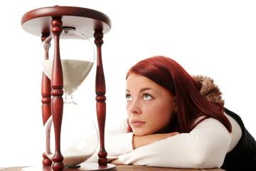 Junge Frau blickt vertraeumt auf große Sanduhr