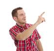 Lachender junger Mann isoliert in Rot zeigt auf etwas