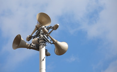 Many loudspeakers against cloudy blue sky