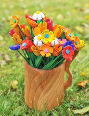 Bouquet multicolored artificial flowers in a vase
