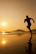 Silhouette of a woman running on th beach.