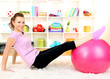 Young woman doing fitness exercises with gym ball at home