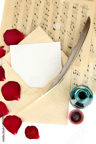 Old envelope with blank paper and dried rose petals