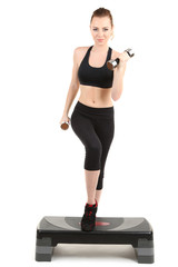 Young woman doing fitness exercises on stepper isolated on