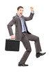 Full length portrait of an excited businessman with a briefcase