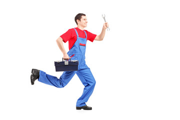 Full length portrait of a repairman running with a wrench and a