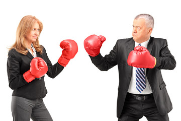 Mature businesswoman with boxing gloves having a fight with a bu