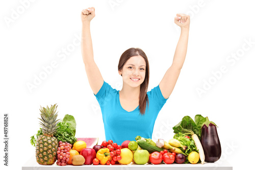 Beautiful young female gesturing happiness on a table full of fr