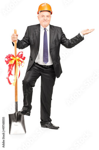 Full length portrait of a mature engineer with a spade