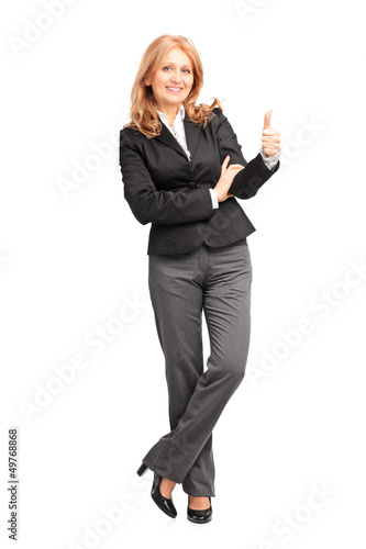 Full length portrait of a smiling businesswoman leaning on wall