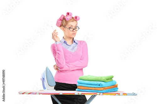 Housewife with hair rollers smoking a cigarette and posing behin