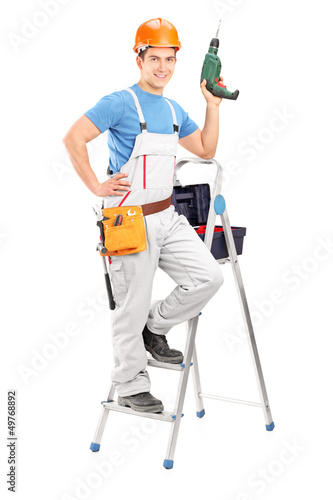 Full length portrait of a repairman with a hand drilling machine
