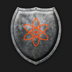 Aged metal shield with the science symbol on carbon background