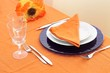 Table setting on orange table cloth