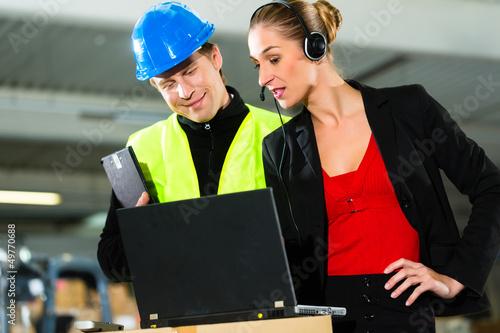 Kollegen im Lager einer Spedition mit laptop