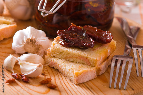 Sliced bread with dried tomato under oil.