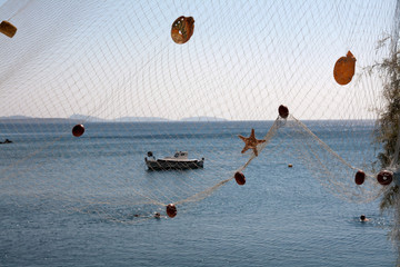Starfish and shel on net, mediterranean sea in the background
