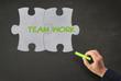 """Puzzle mit Text """"Teamwork"""" auf Kreidetafel"""