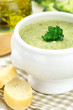 Creamy broccoli soup in a white bowl served with some bread