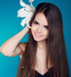 Beautiful woman with long brown hair and white flower. Attractiv