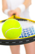 Closeup on ball on racket in hand of tennis player
