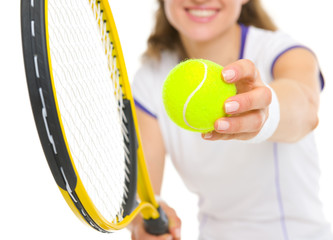 Closeup on racket and ball in hand of tennis player