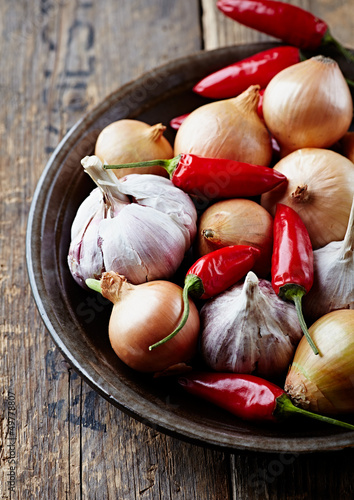 Garlic bulbs, onions and chili peppers on a plate