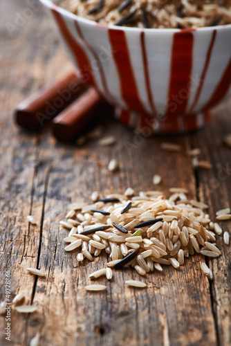 Brown and wild rice on wooden background