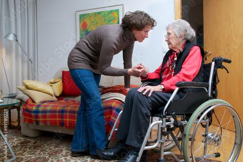 Seniorin im Rollstuhl mit Betreuerin - 49780220