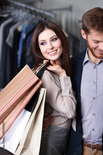Glad beautiful woman is in the shop with her boyfriend
