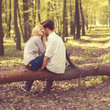 happy young couple kissing and hugging, sitting on a tree