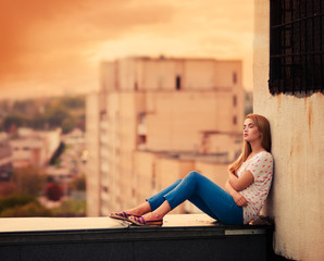 beautiful young girl sitting on the roof