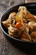 Ripe physalis in a dark ceramic dish