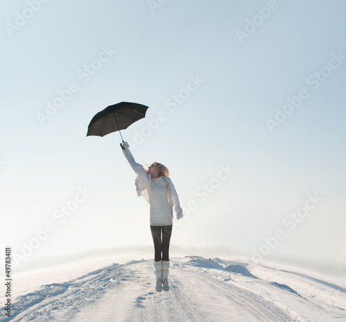 beautiful woman flying with umbrella on road in winter