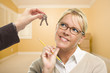Woman Being Handed Keys in Empty Room with Boxes