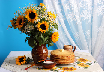 Still life with sunflowers and pancakes