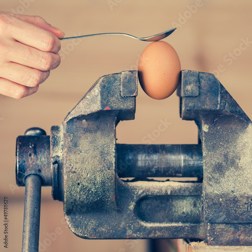 Detail of Hand with Spoon Tapping an Egg Fixed in Vice (color to
