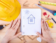 Hands holding paper with drawing a house
