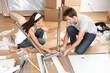 Couple moving in together assembling furniture table