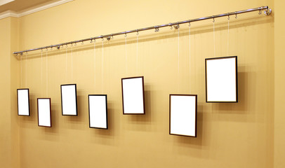 Seven frames with isolated canvas on the exhibition ledge