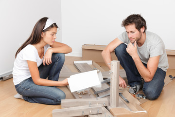 Couple moving in assembling bed furniture