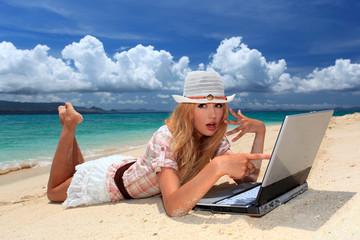 南国沖縄の美しいビーチでパソコンを楽しむ笑顔の女性