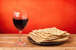 Glass of red wine and matzo on wooden vintage table