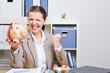 Seniorin mit Sparschwein jubelt im Büro