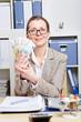 Frau mit Brille hält Geldscheine