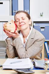 Ältere Frau im Büro mit Sparschwein